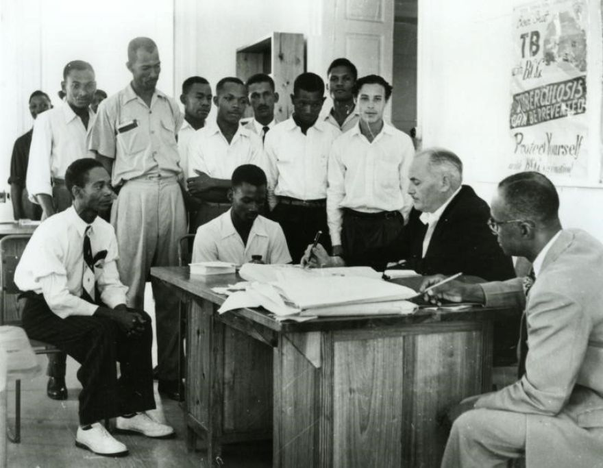 Young Bajan men stand around a desk as a transport manager takes their details