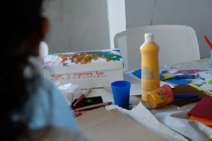 A table covered with art supplies and a decorated box