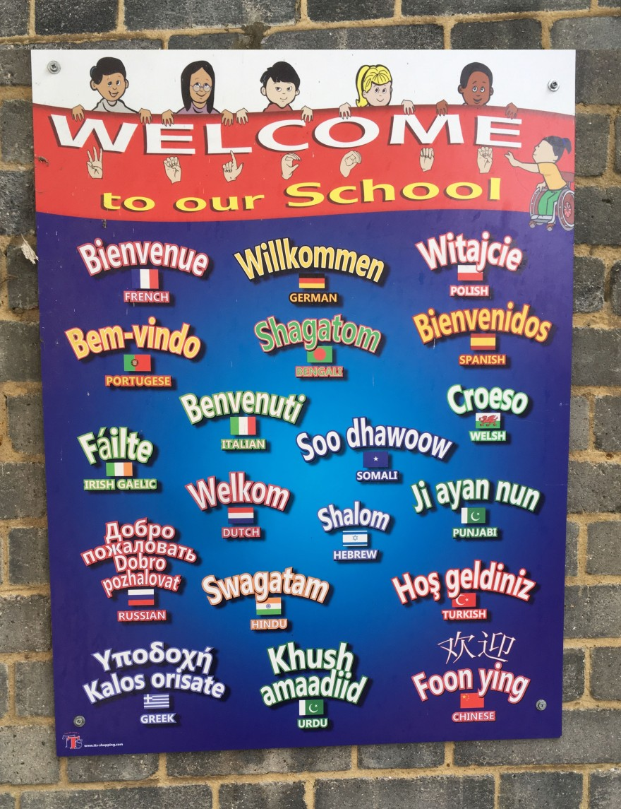 Outdoor sign with welcome written in many different languages