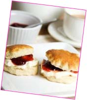 Two scones, jam and cream, with a cup of tea