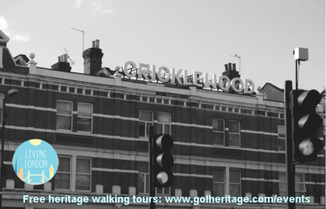 Black and white photo of the Cricklewood sign above shops on Cricklewood Broadway / Edgware Road