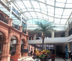 Atrium of the crown hotel with walls of Victorian pub covered by a curved glass ceiling
