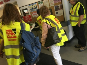 People in bright hi-vis jackets touring inside the bus garage