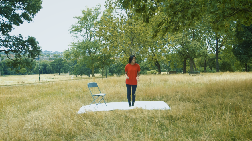 Young woman standing in a park performing lines